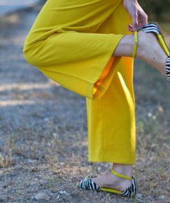 La modelo de Bohemian Shoes viste un pantalón amarillo y unas sandalias de mujer modelo Alizee en animal print cebra