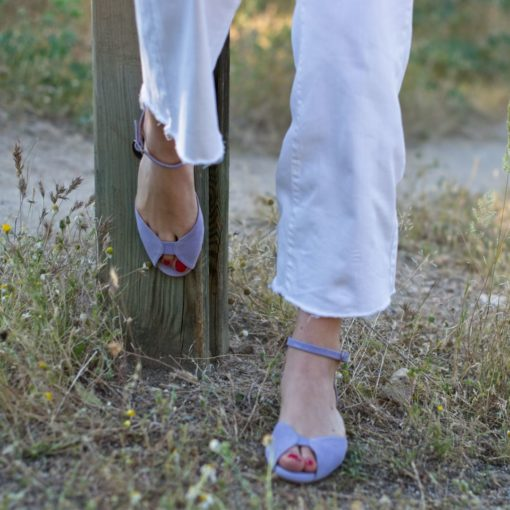 La modelo de Bohemian Shoes posa con un par de sandalias planas modelo Alizée en color malva y unos Jean blancos
