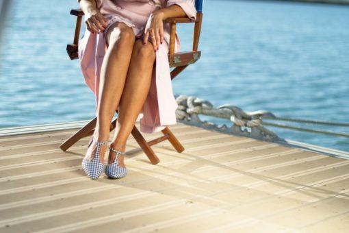 La modelo de Bohemian Shoes posa sentada sentada sobre una silla de madera en un pantalán junto al mar. Viste un vestido de verano rosa y unas Merceditas T-bar de cuadros Vichy negors