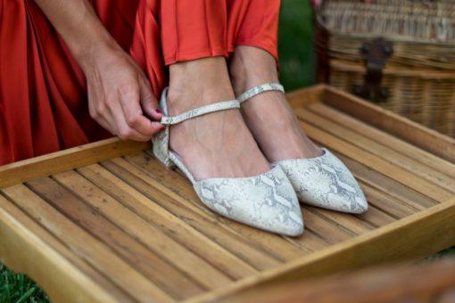 La modelo de Bohemian Shoes se ajusta la tira de sus bailarinas modelo Adèle, fabricadas en piel con estampado de serpiente