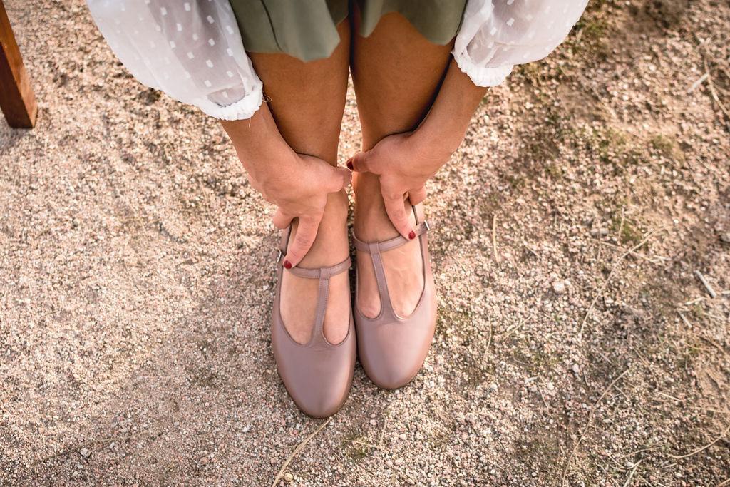 Las piernas de la modelo de Bohemian Shoes calza unos zapatos de mujer tipo Mercedita T-bar, modelo Odette, color terracota. Agarra los tobillos con sus manos y viste un pantalón color verde oliva