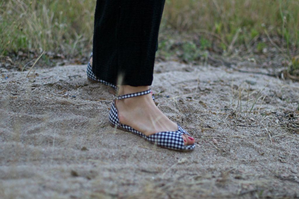 La modelo de Bohemian posa de pie con un mono negro. Calza unas sandalias planas en Vichy negro sobre un camino que va a la playa