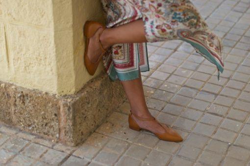 La modelo de Bohemian está apoyada sobre una columna. Calza un par de Merceditas modelo Juliette color cuero
